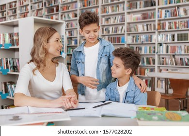 Two twin brothers and their mam enjoying studying together at the library. Beautiful woman helping her kids with homework