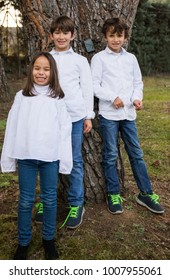 two twin brothers and a younger sister posing next to a tree in the garden of the house