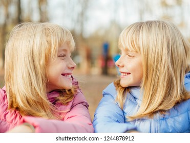 Two twin sisters girls watching each other
