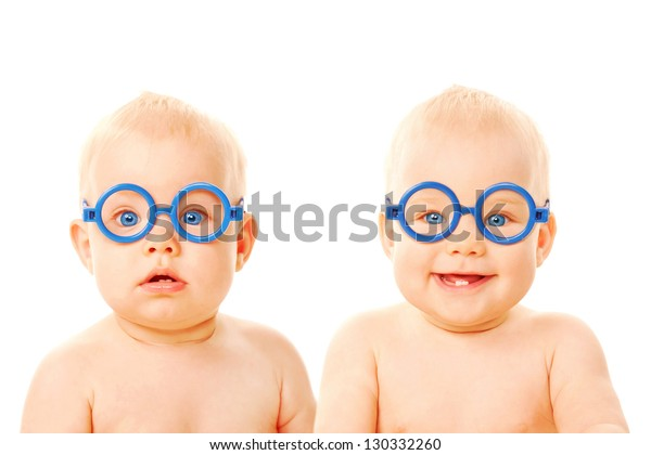 Two twins babies boys wearing glasses. One kid serious, the other child smiling. Young students. Isolated on white background