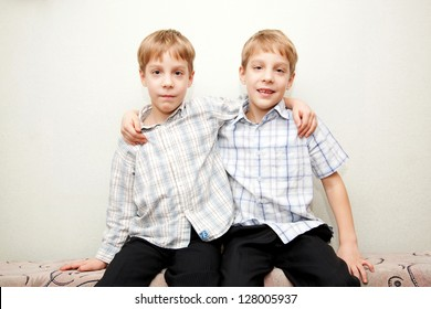 Two twins brothers wearing checkered shirt hugging and smiling.