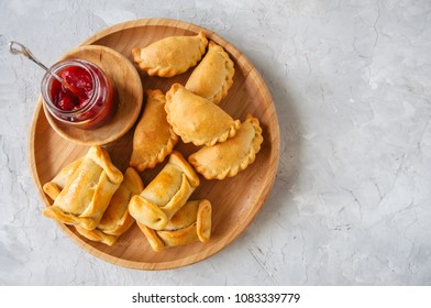 Two types of empanadas on a wooden plate with ketchup