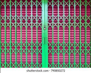 Two types of folding metal door. Close and locked of green and dark pink folding metal doors. Folding door pattern or texture.