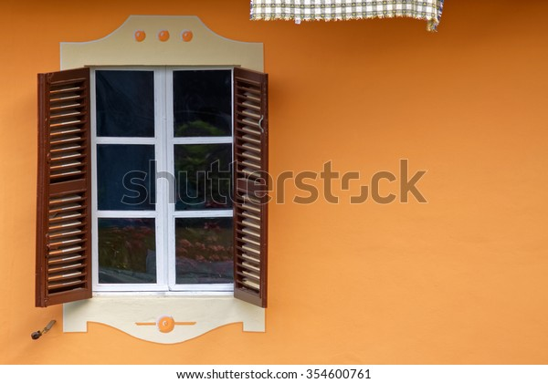 Two typical italian shutters and window to orange wall