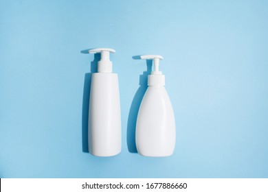 Two typy of white plastic bottles on blue background with hard light. Mockup. Means of protection. Liquid soap, sanitazer gel for hands. Flat lay. Hygiene for shower and bath