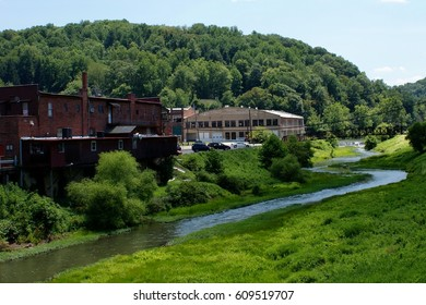Two ugly buildings on the edge of a small Appalachian town sit beside the bank of a beautiful small river winding through the hills and woods of a beautiful surrounding landscape.