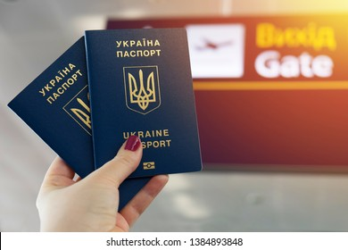 Two ukrainian biometric passports in a hand. Airport signs on background.