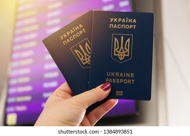 Two ukrainian biometric passports in a hand. Airport timetable on background.