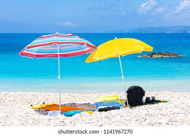 Two umbrellas with beddings on the white beach