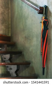 Two umbrellas hanging on banisters beside wood stairs, the big is orange and black colors, the small is orange color.