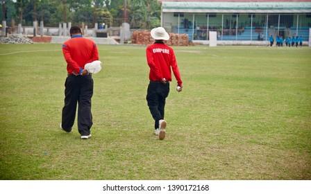Two umpires wearing red shirt walking around a ground