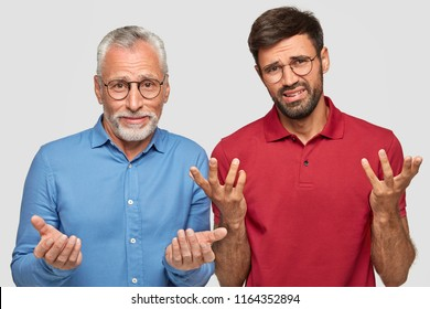 Two uncertain collaborators gesture with hesitation, dont know how solve problem, have clueless expressions, stand next to each other, isolated over white background. Mature man and his subordinate