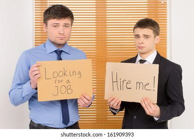 Two unemployed men looking for a job.  Showing plates with sing asking for vacant position