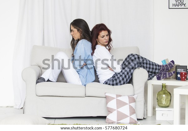 Two unhappy young girls having conflict at home