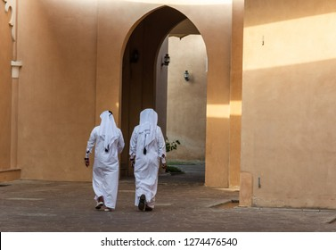 Two unidentifiable Arabic men in white thobe clothing walking away in Doha, Qatar.