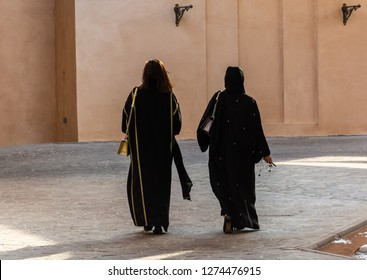 Two unidentifiable Arabic women wearing traditional Islamic black dress  walking away, from the back. One with covered and one with uncovered head.