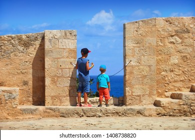 Two unidentified boys look through the loopholes of Fortezza of Rethymno (Rethimno Fortress), Crete island, Southern Greece, Europe. View from the wall of ancient Venetian fort, blue water and sky