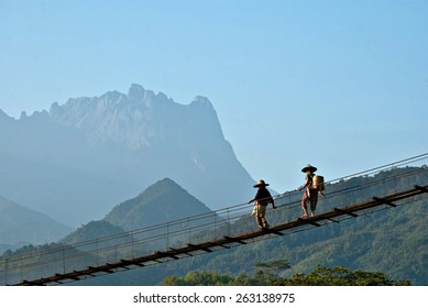 Two unidentified couple of elderly farmers at Kota Belud, Sabah are walking on a suspension bridge on an early morning, with Mount Kinabalu as background