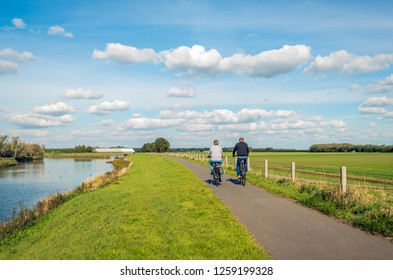 Two unidentified people cycle on a cycle path at the top of a dike along a narrow river at the Dutch National Park De Biesbosch in the province of Noord-Brabant.