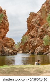 Two unidentified woman sitting at a water pool in West MacDonnell National Park in NT central outback Australia.