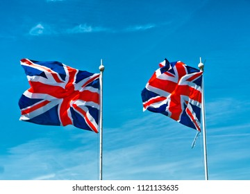 Two Union Jack Flags flying in wind; British 'Union Jack' flag flying in the wind against a summer sky