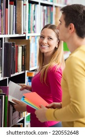 Two university students picking books from library shelves.
