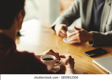 Two unrecognizable businessmen having business talk over coffee sitting at table in cafe. Laptop, coffee cups and smartphone on table. Focus on hands and cup of espresso