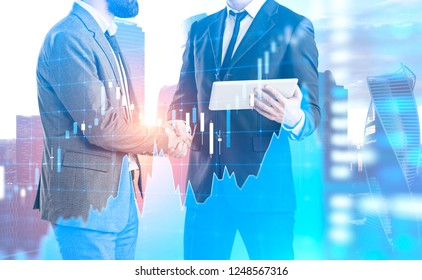 Two unrecognizable businessmen shaking hands. One of them is holding tablet standing over Moscow city background with blue graph interface foreground. Toned image double exposure