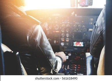 Two unrecognizable jet airliner pilots wearing leather jackets piloting aircraft at sunset, sitting inside cabin at steering control with modern dashboard, sun shining through cockpit windscreen