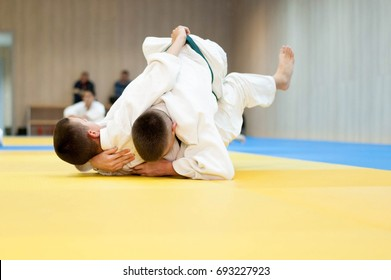 Two unrecognizable judokas fighting on the ground