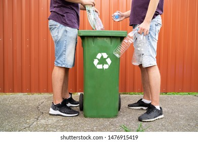 Two unrecognizable man throwing plastic bottles in recycle bin