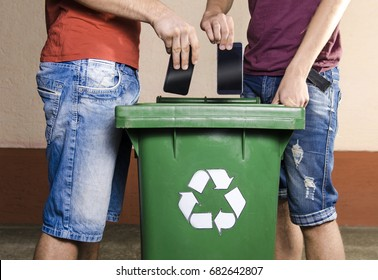 Two unrecognizable man throwing smartphones in recycle bin , outdated, obsolete technology
