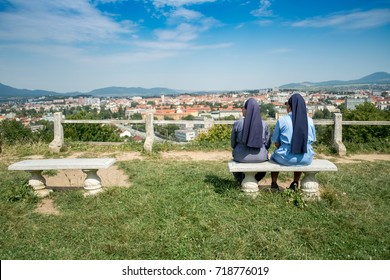 Two (unrecognizable) nuns sitting on a bank, contemplating, looking at a distant city