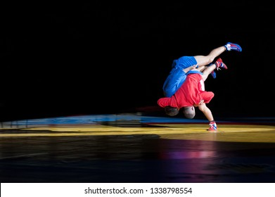 Two unrecognizable russian style wrestlers demonstrating throwing technique