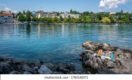 Two unrecognizable young women sun tanning on the shores of Lake Geneva and city view in Ouchy district Lausanne Vaud Switzerland