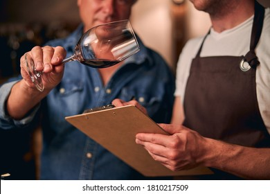 Two unrecognized sommeliers in a winery making notes on a clipboard while evaluating red wine in a glass