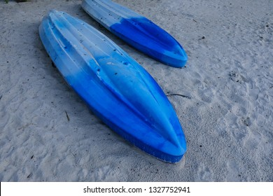 Two upside down blue kayaks laying on a white sand beach.