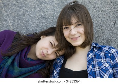 two urban teen girls standing at wall.