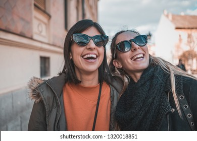 Two urban woman friends in city having fun. Two  hipster females in town walking and talking