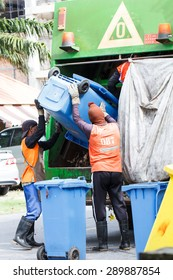 Two urban workers municipal recycling garbage collector truck loading waste and trash bin