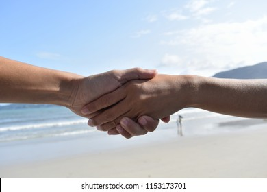 The two of us hold hands. For business contracts The background is beautiful sea.