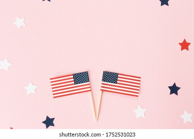 Two usa flag toothpick and star around on pink background, flat lay. 4th of july in America, celebration independence day in usa. Copy space for text in center.