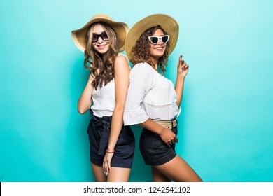 Two vacation girls with different color of skin wearing straw hats and summer clothing rejoicing their holiday isolated over blue background