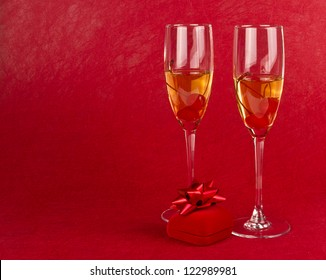 Two Valentine champagne glasses with jewelry box on red background