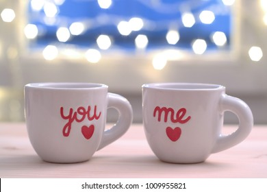 Two valentine's coffee mugs on wooden table with red hearts and word you and me, and light bokeh on background
