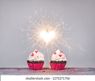Two valentines day buttercream Cupcakes with sparklers creating a heart shape celebrating love concept
