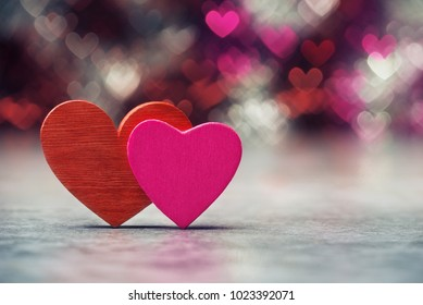 Two Valentines hearts over holiday abstract background.