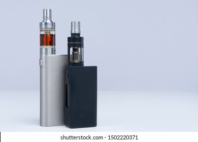 Two vapes on a white background. The concept of vaping. VAPE shop. Smoking electronic cigarettes. Sale of e-cigarettes. Place for inscription. Two models of electronic cigarettes.