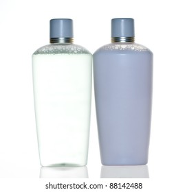two various blank cosmetic containers with reflections on white background