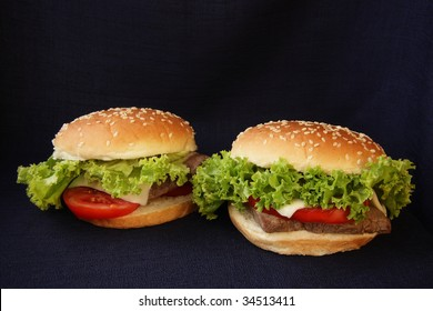 Two veal burgers on a dark background.